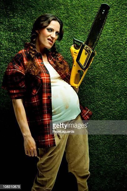 Nerd pregnant lumberjack holding a chainsaw