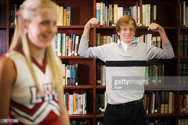 Nerd Showing Off Muscles to Cheerleader