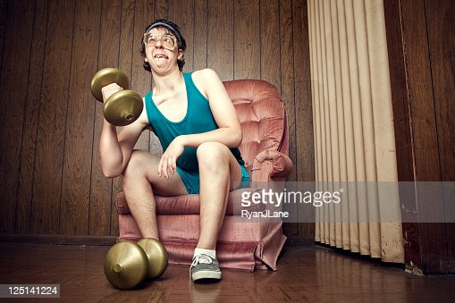 Nerd Young Man Exercising with Weights : Stock Photo