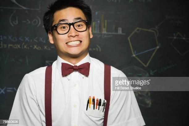 Nerdy Asian male student in front of blackboard