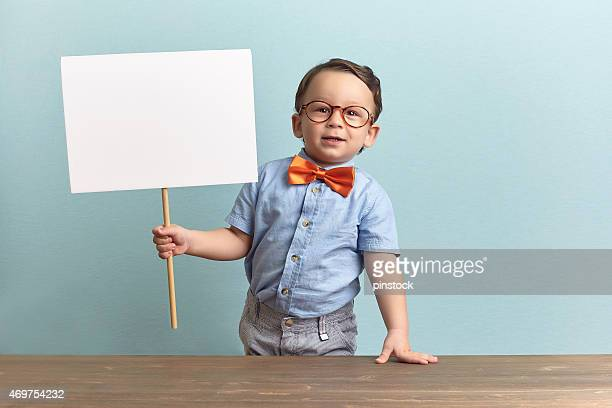 Nerdy child holding a blank sign in a classroom