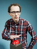 A nerdy guy with his hand poised above a red game show buzzer