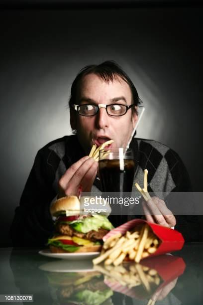 Nerd homem comer hambúrguer e batatas fritas