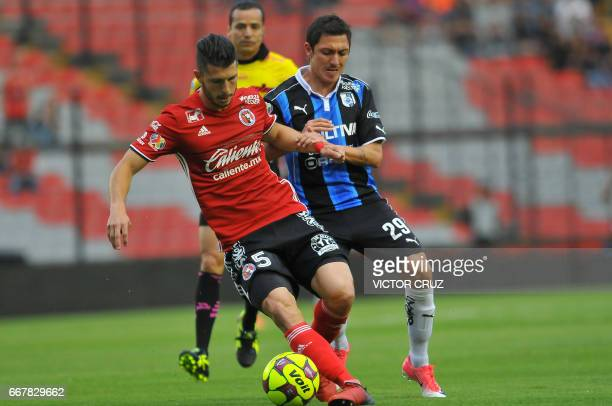 Neri Cardozo of Queretaro vies for the ball with Guido Rodriguez of Tijuana during their Mexican Clausura 2017 Tournament football match at La...