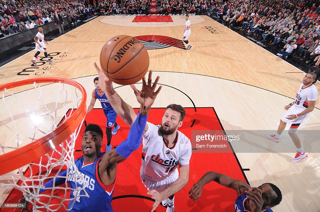 Nerlens Noel of the Philadelphia 76ers and Joel Freeland of the Portland Trail Blazers go up for a rebound on December 26 2014 at the Moda Center...