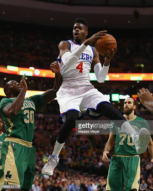Nerlens Noel of the Philadelphia 76ers takes a shot over Brandon Bass of the Boston Celtics during the first quarter at TD Garden on March 16 2015 in...