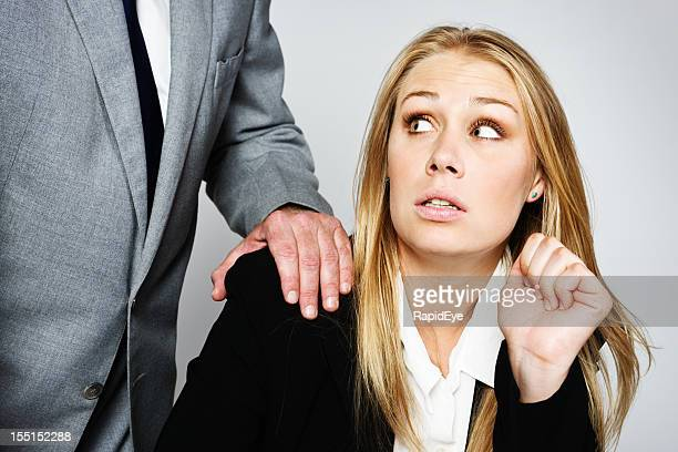 Nervous blonde businesswoman shrinks from businessman's hand