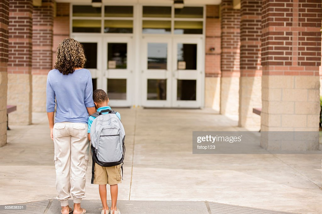 Nervous boy. First day of school.  Holds on to mom. : Stock Photo