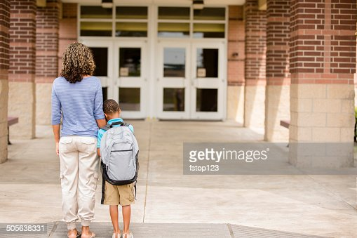 Nervous boy. First day of school.  Holds on to mom.