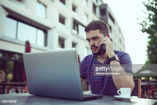 Nervous  Freelancer Working and Talking on the Phone at his Favorite Coffee Place