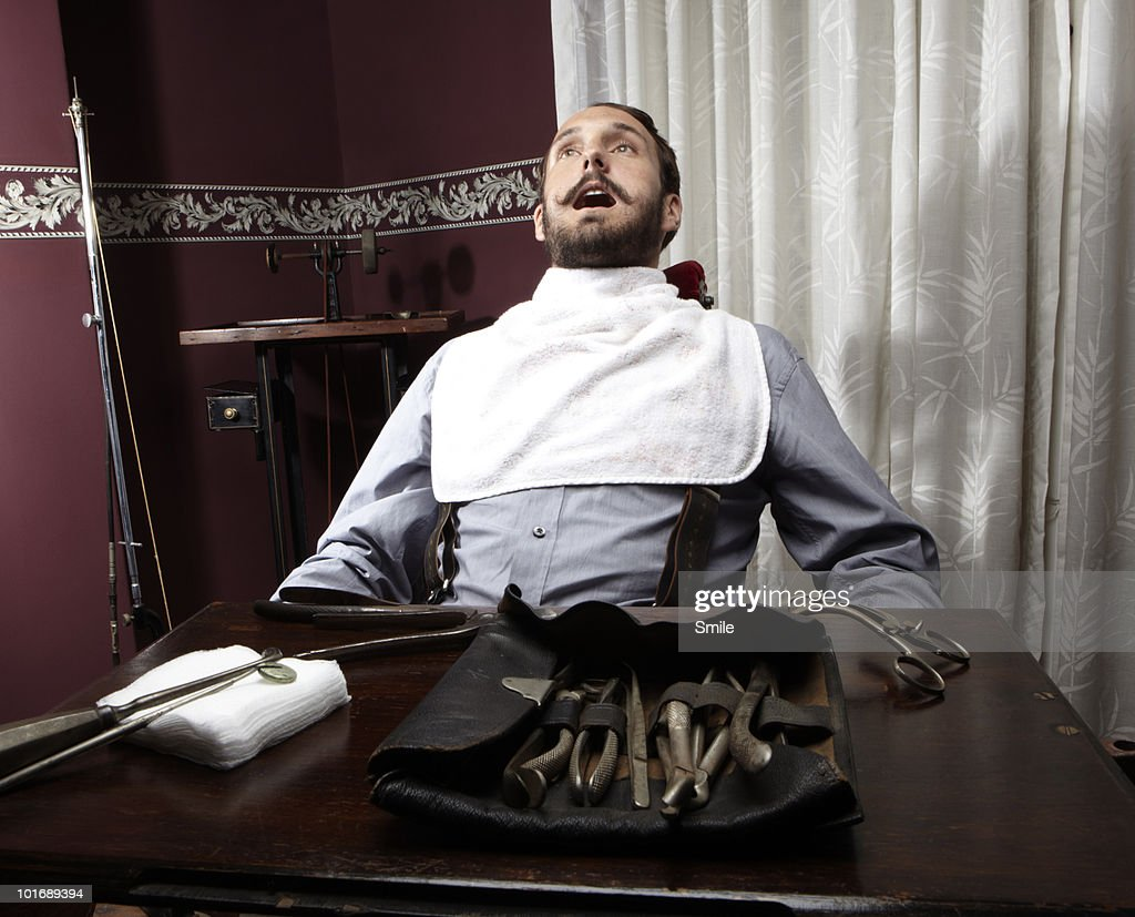 Nervous man in dentist chair : Stock Photo