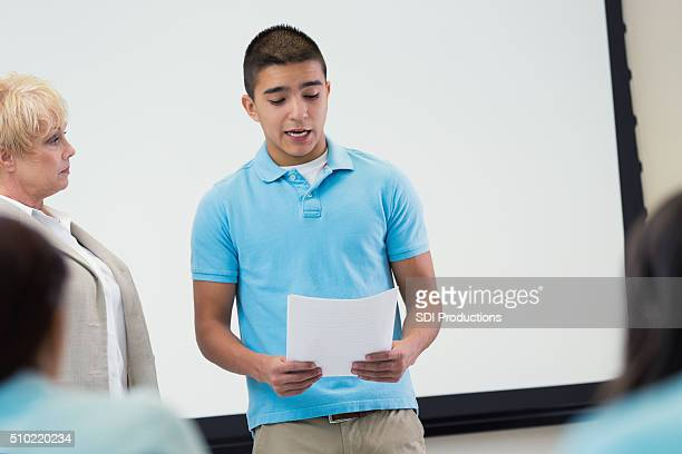 Nervous private high school student reads report to class