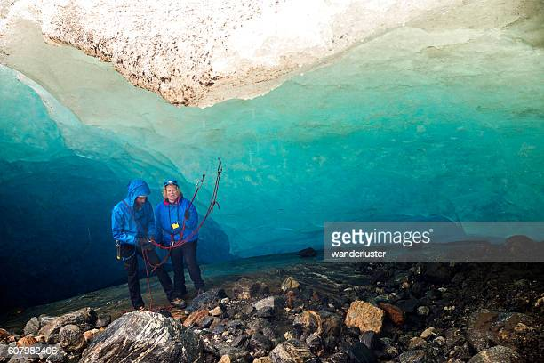 Nervous woman prepares to rappel in ice cave