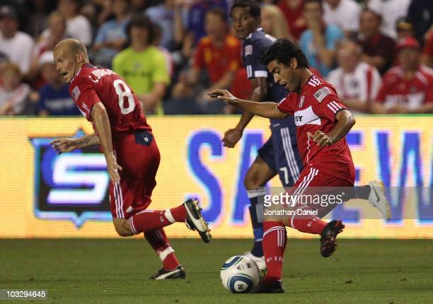 Nery Castillo of the Chicago Fire passes the ball to Freddie Ljungberg as Roy Miller of the New York Red Bulls defends in an MLS match on August 8...