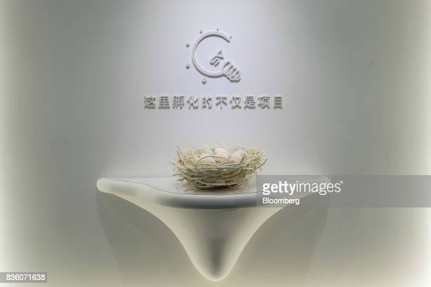 A nest of illuminated eggs sit on display beneath a light bulb icon at the entrance to the Sinovation Ventures headquarters in Beijing China on...