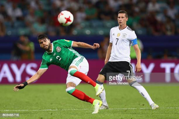 Nestor Araujo of Mexico clears the ball in front of Julian Draxler of Germany during the FIFA Confederations Cup Russia 2017 SemiFinal between...