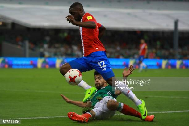 Nestor Araujo of Mexico struggles for the ball with Joel Campbell of Costa Rica during the fifth round match between Mexico and Costa Rica as part of...
