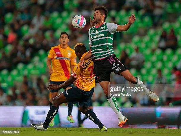 Nestor Araujo of Santos and Duvier Riascos of Morelia fight for the ball during a match between Santos Laguna and Morelia as part of 12th round...