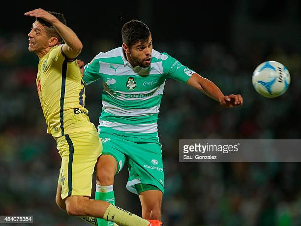 Nestor Araujo of Santos and Oribe Peralta of America jump for the ball during a 5th round match between Santos Laguna and America as part of the...