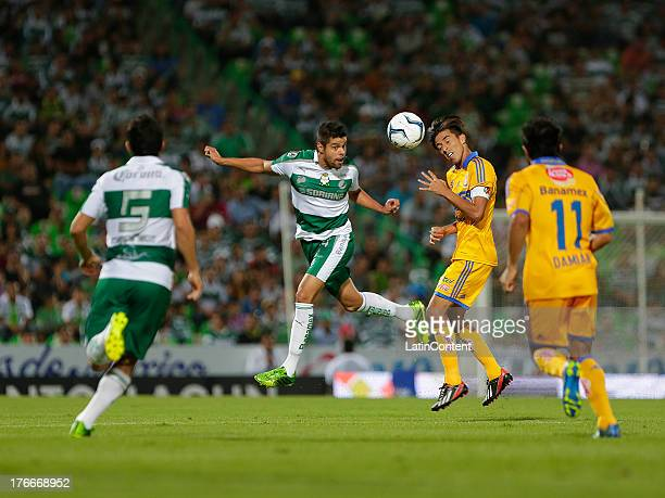 Nestor Araujo of Santos fights for the ball with Lucas Lobos of Tigres during a match between Santos and Tigres as part of Apertura 2013 Liga...