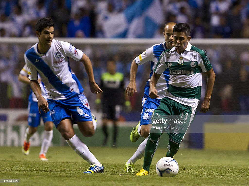 Nestor Calderon of Santos competes for the ball with Diego Buen of Puebla during a match between Puebla and Santos as part of the Torneo de Apertura 2013 Liga MX Championship at Cuauhtemoc Stadium, on July 31, 2013 in Puebla, Mexico.