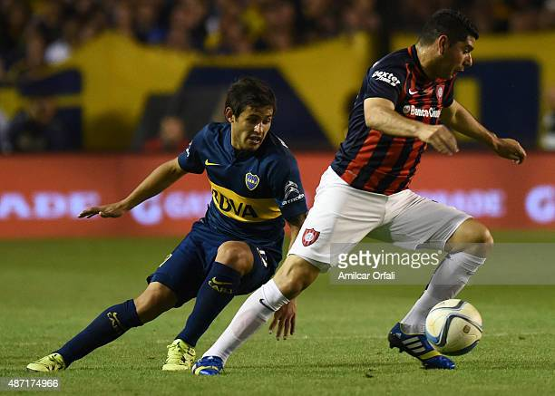 Nestor Ortigoza of San Lorenzo controls the ball as Marcelo Meli of Boca Juniors chases him during a match between Boca Juniors and San Lorenzo as...