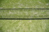 Net of a tennis court projecting its shadow on the grass, background with green texture.