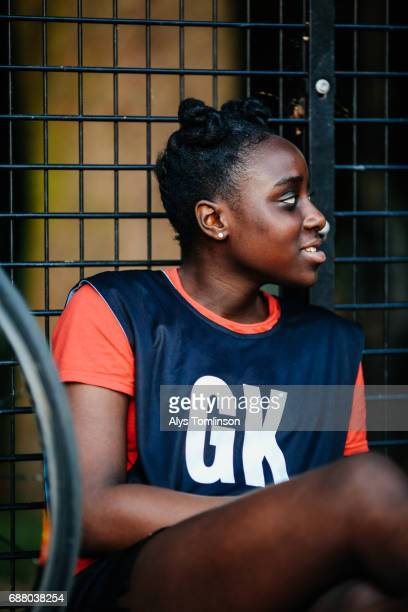 netball player looking sideways and sitting by the side of outdoor, city sports court