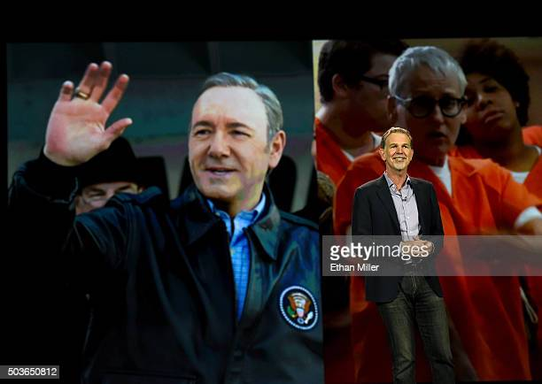 Netflix CEO Reed Hastings delivers a keynote address in front of an image of actor Kevin Spacey from 'House of Cards' and an image from the show...