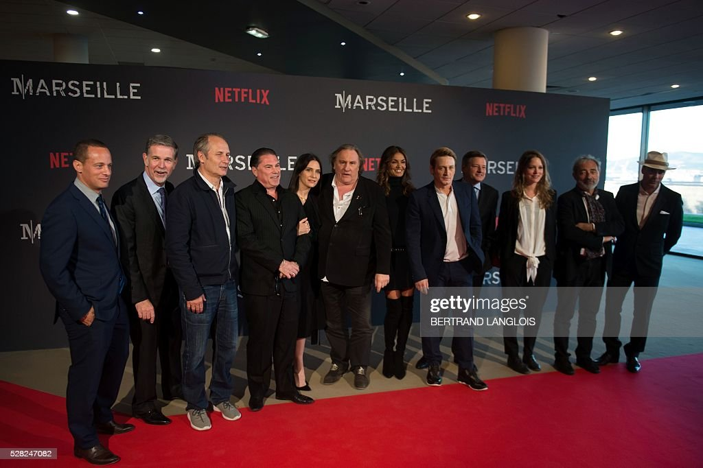 Netflix co-founder and CEO Reed Hastings (2rd L), Netflix Chief content officer Ted Sarandos (4th R), Netflix vice president international originals Erik Barmack (L), visual creator and director Florent Siri (4th L), French actors Hippolyte Girardot (3rd L), Geraldine Pailhas (5th M), Gerard Depardieu (C), Nadia Fares (6th R), Benoit Magimel (5th R), Stephane Caillard (3rd R), writer Dan Franck and producer Pascal Breton pose during a photocall for the premiere of the French TV show 'Marseille' broadcasted and co-produced by Netflix on May 4, 2016 in Marseille, southern France. / AFP / BERTRAND