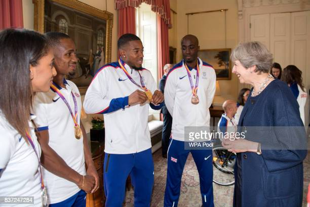 Nethaneel MitchellBlake shows his Gold medal for winning 4x100 metre relay to British Prime Minister Theresa May a reception for who competed in the...