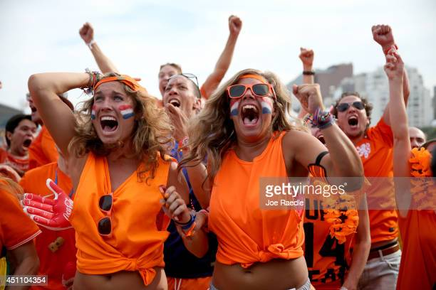 Netherland soccer fans react as their team scores their second goal against Chile as they watch on a screen setup at the FIFA Fan Fest on Copacabana...