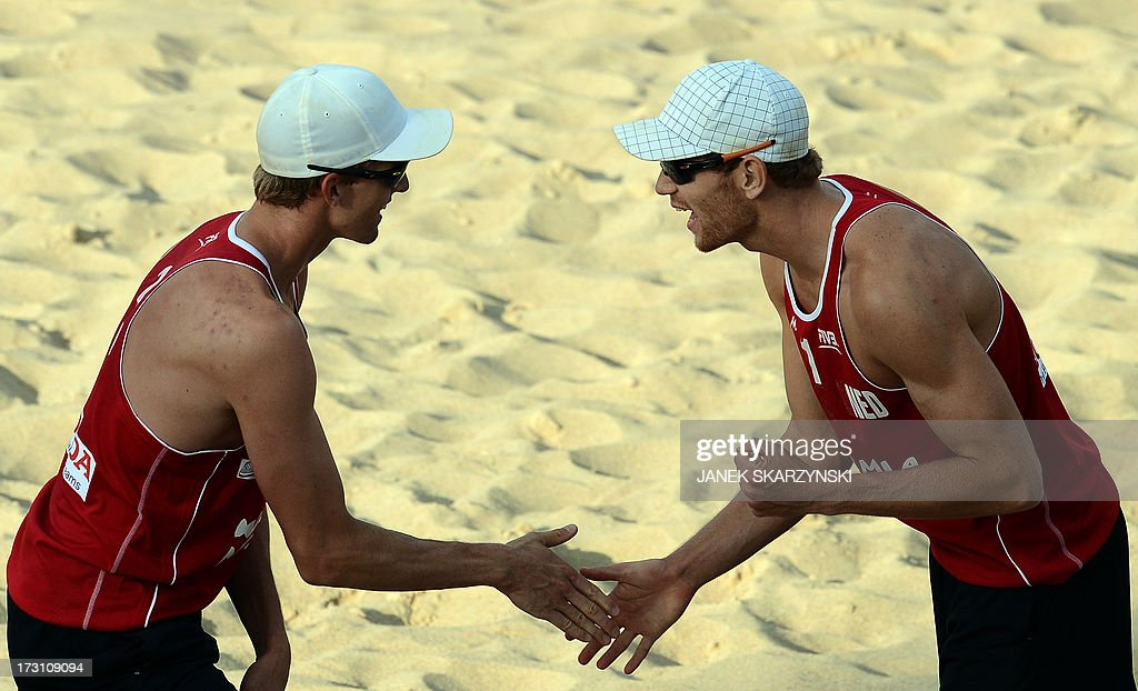 Netherland's Alexander Brouwer (R) and Robert Meeuwsen (L) cheer after they defeated Brazil's Ricardo Alex Costa Santos and Alvaro Morais Filho (not pictured) during the final match of the Beach Volleyball World Championships on July 7, 2013 in Stare Jablonki, Poland.