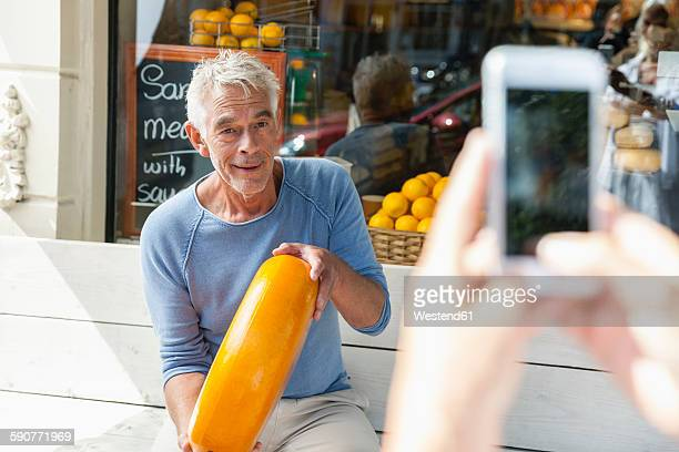 Netherlands, Amsterdam, cell phone picture of senior man sitting on bench holding loaf of cheese