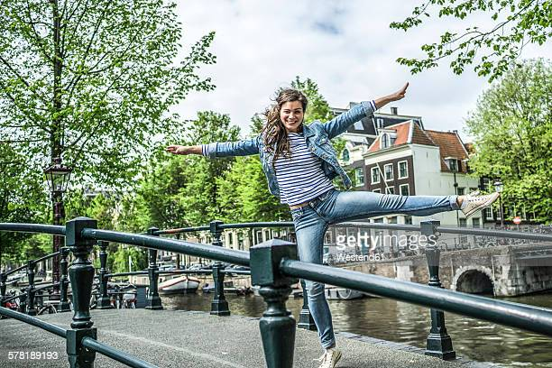 Netherlands, Amsterdam, female tourist balancing on one leg on a footbridge