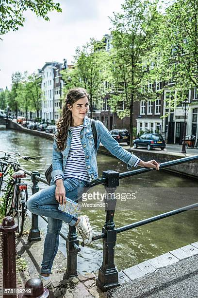 Netherlands, Amsterdam, female tourist lwith city map in front of town canal