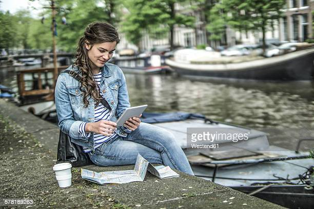Netherlands, Amsterdam, female tourist using digital tablet in front of town canal