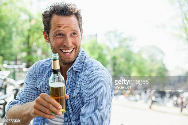 Netherlands, Amsterdam, happy man drinking beer from bottle