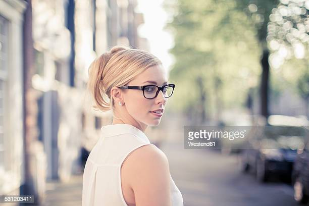 Netherlands, Amsterdam, portrait of young woman wearing glasses