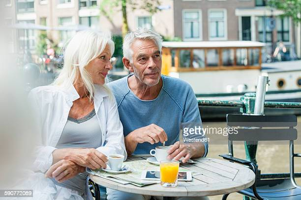 Netherlands, Amsterdam, senior couple in an outdoor cafe