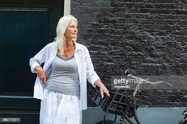 Netherlands, Amsterdam, senior woman standing with bike in front of house