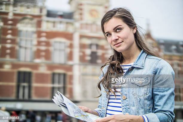 Netherlands, Amsterdam, woman with city map in front of central station