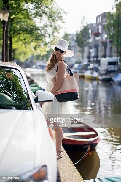 Netherlands, Amsterdam, young woman standing besides a car in front of a town canal