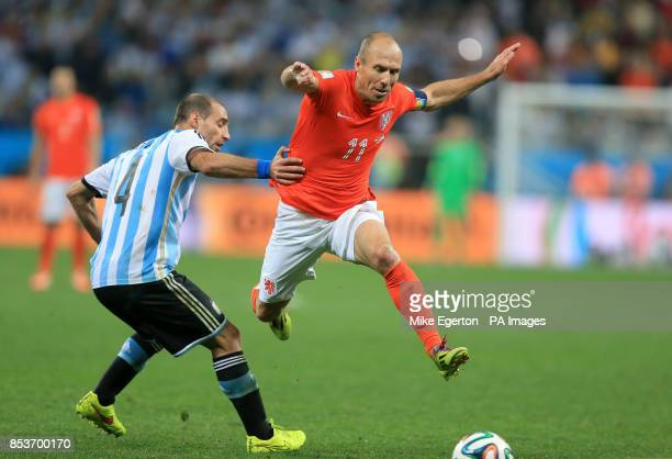 Netherlands' Arjen Robben hurdles a challenge from Argentina's Pablo Zabaleta during the FIFA World Cup Semi Final at the Arena de Sao Paulo Sao...