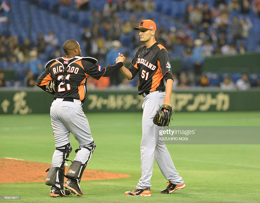 Netherlands' battery, catcher Dashenko Ricardo (L) and pitcher Loek Van Mil (R) celebrate their win over Cuba after the second-round Pool 1 game in the World Baseball Classic tournament at Tokyo Dome on March 8, 2013. Netherlands beat Cuba 6-2. AFP PHOTO / KAZUHIRO NOGI