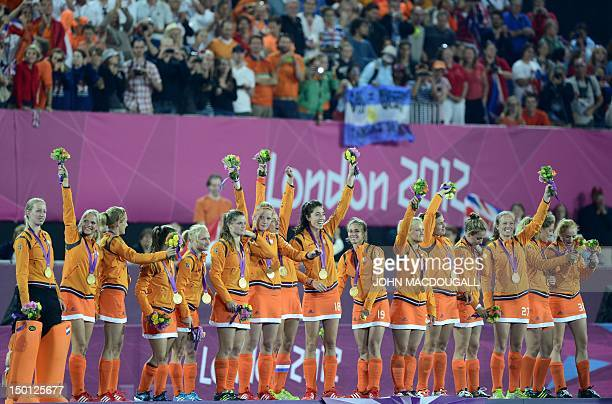 Netherlands captain Maartje Paumen and teammates wave from the podium as they celebrate victory after the women's field hockey gold medal match...