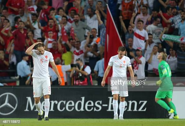 Netherlands' Daley Blind gestures as Turkey's players celebrate after scoring a goal during the Euro 2016 qualifying football match between Turkey...