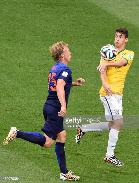 Netherlands' defender Dirk Kuyt and Brazil's midfielder Oscar vie for the ball during the third place playoff football match between Brazil and...