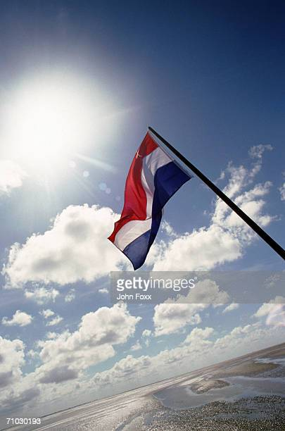 Netherlands, Dutch flag against sky, low angle view