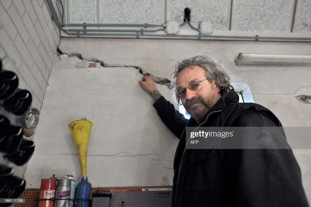 Netherland's Elze Schollema shows on March 12 2013 a crack in his garage wall in Usquert some 25km from Groningen caused by an earthquake in February...